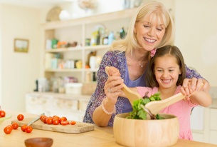 Grandmother and granddaughter tossing salad in kitchenの写真素材 [FYI02169997]