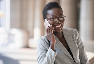Smiling corporate businesswoman talking on cell phoneの写真素材 [FYI02170110]