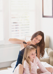 Mother brushing daughter's hair on bedの写真素材 [FYI02170118]