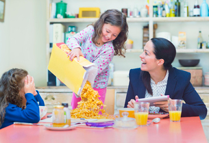 Playful girl pouring abundance of cereal onto breakfast tableの写真素材 [FYI02170143]