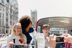 Friends with map riding double-decker bus, London, United Kingdomの写真素材 [FYI02170176]
