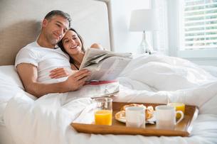 Smiling couple reading newspaper enjoying breakfast in bedの写真素材 [FYI02170248]