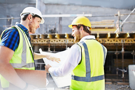Construction worker and engineer reviewing blueprints at construction siteの写真素材 [FYI02170260]