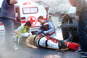 Rescue workers tending to car accident victim in roadの写真素材 [FYI02170266]