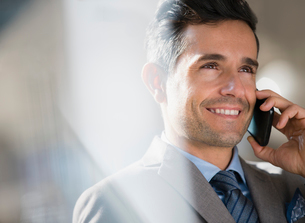 Close up smiling corporate businessman talking on cell phoneの写真素材 [FYI02170303]
