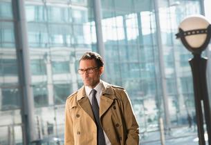 Corporate businessman in trench coat looking awayの写真素材 [FYI02170305]