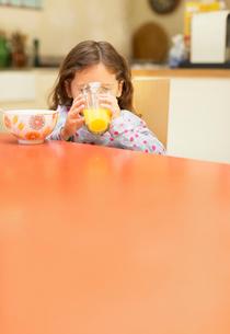 Girl drinking orange juice at breakfast tableの写真素材 [FYI02170331]