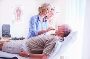 Doctor examining senior man's mouth at checkupの写真素材 [FYI02170341]