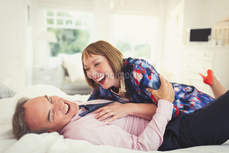 Well-dressed mature couple laughing on bedの写真素材 [FYI02170355]