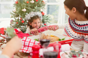 Mother and daughter pulling Christmas cracker at dinner tableの写真素材 [FYI02170389]