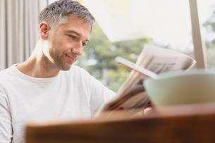 Man reading newspaper at breakfastの写真素材 [FYI02170410]