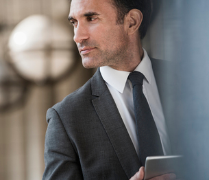 Pensive corporate businessman with digital tablet looking awayの写真素材 [FYI02170449]