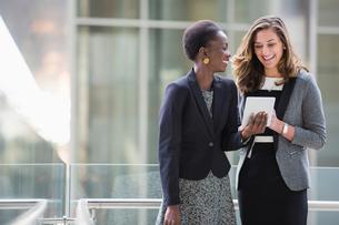 Smiling corporate businesswomen using digital tabletの写真素材 [FYI02170463]