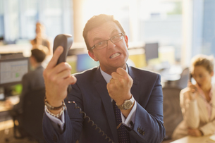 Furious businessman gesturing with fist at telephone in officeの写真素材 [FYI02170486]