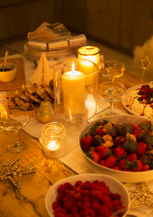 Food and decorations on candlelight Christmas tableの写真素材 [FYI02170493]