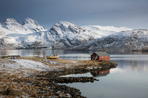 Fishing hut on cold bay below snow covered mountains, Norwayの写真素材 [FYI02170513]
