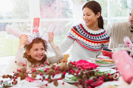 Playful girl holding Christmas crackers on head at tableの写真素材 [FYI02170516]