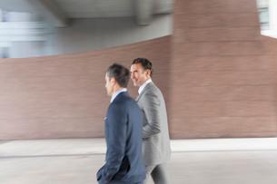 Corporate businessmen walking outside buildingの写真素材 [FYI02170528]