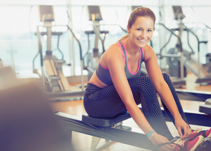 Portrait smiling woman tying shoe on rowing machine at gymの写真素材 [FYI02170534]