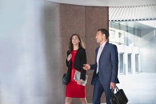 Corporate businessman and businesswoman talking and walking outdoorsの写真素材 [FYI02170538]