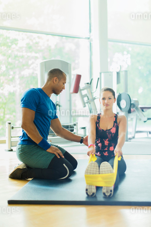 Personal trainer guiding woman stretching legs with resistance band at gymの写真素材 [FYI02170544]