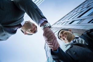 Corporate businessmen handshaking below buildingの写真素材 [FYI02170546]