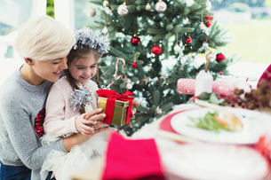 Smiling mother and daughter with Christmas giftの写真素材 [FYI02170550]