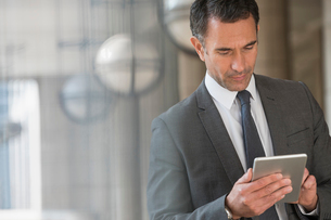 Corporate businessman using digital tablet outdoorsの写真素材 [FYI02170559]