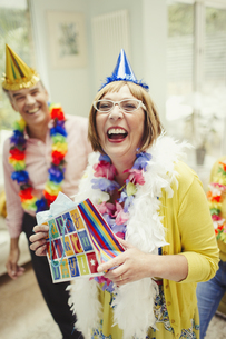 Portrait laughing mature woman in party hat holding birthday giftの写真素材 [FYI02170578]