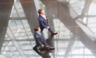 Corporate businessmen walking in modern office lobbyの写真素材 [FYI02170587]