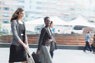 Portrait smiling corporate businesswoman walking outdoorsの写真素材 [FYI02170627]