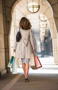 Businesswoman with shopping bags walking in cloisterの写真素材 [FYI02170648]