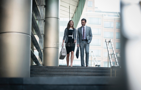 Corporate businessman and businesswoman descending stairs outdoorsの写真素材 [FYI02170663]