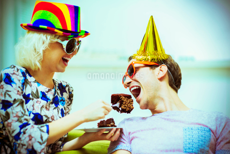Playful couple in party hats and sunglasses eating chocolate cakeの写真素材 [FYI02170710]
