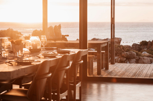 Sunny home showcase dining room overlooking ocean at sunsetの写真素材 [FYI02170725]