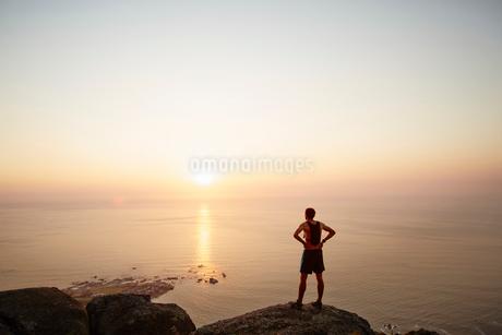 Male runner on rocks looking at sunset ocean viewの写真素材 [FYI02170761]