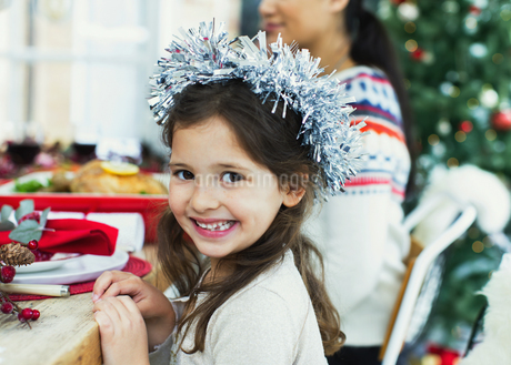 Portrait enthusiastic girl wearing wreath at Christmas dinnerの写真素材 [FYI02170778]