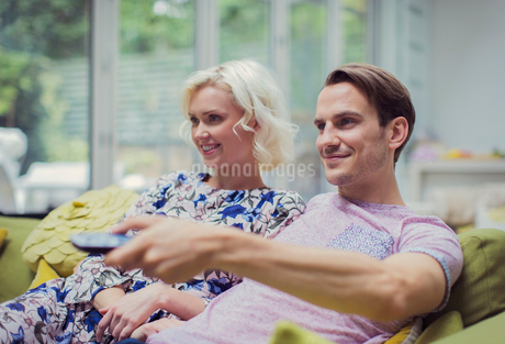 Smiling couple watching TV in living room changing channelsの写真素材 [FYI02170795]