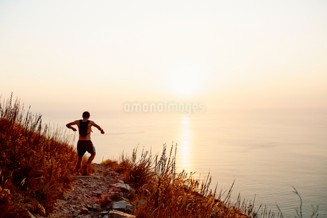 Male runner with backpack descending craggy trail overlooking sunset oceanの写真素材 [FYI02170812]