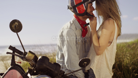Affectionate young couple at motorcycle with beach in backgroundの写真素材 [FYI02170819]