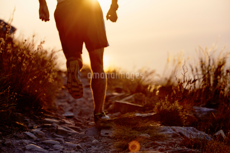 Man running on craggy trail at sunsetの写真素材 [FYI02170837]