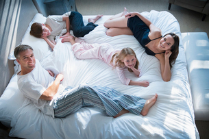 Portrait smiling family in pajamas relaxing on bedの写真素材 [FYI02170844]