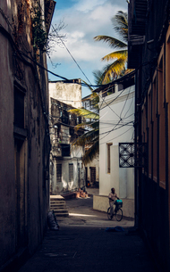 Man riding bicycle on narrow street between buildings, Zanzibar, Tanzaniaの写真素材 [FYI02170859]