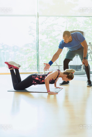 Personal trainer guiding woman doing push-ups on knees at gymの写真素材 [FYI02170867]