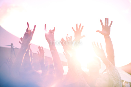 Arms raised cheering at sunny music festivalの写真素材 [FYI02170868]