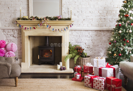 Christmas tree, gifts and decorations near fireplace in living roomの写真素材 [FYI02170875]