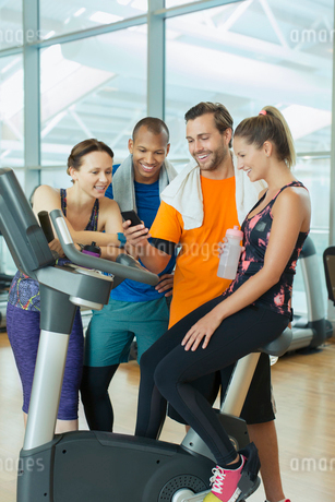Friends using cell phone at exercise bike in gymの写真素材 [FYI02170885]