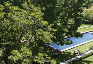 Woman sitting on lawn chair next to sunny swimming pool under green summer treesの写真素材 [FYI02170946]