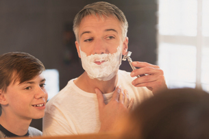 Son watching father shave face in bathroom mirrorの写真素材 [FYI02170970]