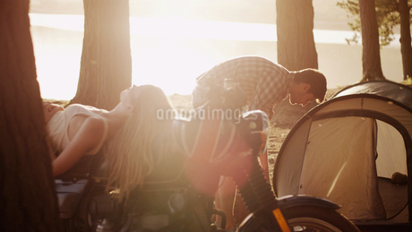Young man preparing tent at campsite next to woman laying on motorcycleの写真素材 [FYI02170992]